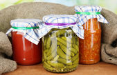 Jars with canned vegetables on green background close-up — Stock Photo