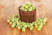 Green gooseberry in wooden cup on wooden background — Stock Photo