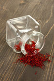 Stigmas of the saffron poured out a glass jar on wooden background close-up — Stock Photo