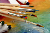 Acrylic paint, paint tubes and brushes on wooden palette — Stock Photo