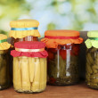 Jars with canned vegetables on green background close-up — Stock Photo #12201395
