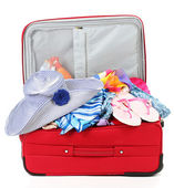 Suitcase with summer clothes, a hat and suntan isolated on white — Stock Photo