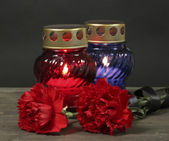 Memory lantern with candles, red carnations and ribbon on wooden table on grey background — Stock Photo