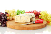 Cheese with mold on the cutting board with grapes on white background close-up — Stock Photo