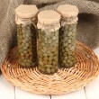 Glass jars with tinned capers in sack on white wooden background — Stock Photo #12219737