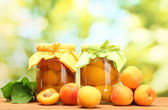 Canned apricots in a jars and sweet apricots on wooden table on green background — Stock Photo