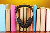 Cuffie su libri sul tavolo di legno su sfondo giallo — Foto Stock