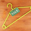Coat hanger with sale tag on wooden background — Stock Photo