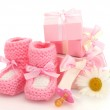 Pink baby boots, pacifier, gifts and flower isolated on white — Stock Photo