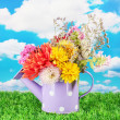 Stock Photo: Purple watering cwith white polka-dot with flowers on sky background