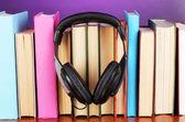 Hörlurar på böcker om träbord på lila bakgrund — Stockfoto