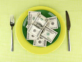 Banknotes on the plate on green tablecloth close-up — Stock Photo