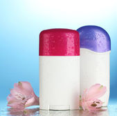 Deodorants with flowers on blue background — Stock Photo