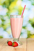 Strawberry milk shake op houten tafel op lichte achtergrond — Stockfoto