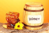 Barrel of honey and honeycomb on wooden table on orange background — Stock Photo