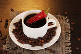 Coffee and pepper on wooden table on brown background — Stock Photo