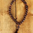 The Wooden rosary beads on wooden background close-up - Stock Photo