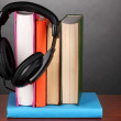 Headphones on books on wooden table on black background — Stock Photo
