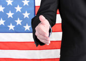 Businessman giving his hand for a handshake on American flag background — Stock Photo