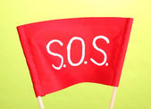 SOS signal written on red cloth on green background — Photo