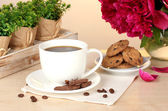 Cup of coffee, cookies, chocolate and flowers on table in cafe — Stock Photo