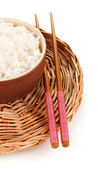 Bowl of rice and chopsticks on wicker mat isoalted on white — Stock Photo