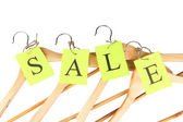 Coat hangers with sale tag on white background close-up — Stock Photo