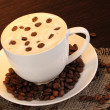 Latte on wooden table on brown background - Photo