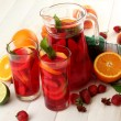 Sangria in jar and glasses with fruits, on white wooden table — Stock Photo #12271685