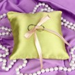Wedding rings on satin pillow on purple cloth background — Foto de Stock