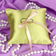 Wedding rings on satin pillow on purple cloth background — Stock fotografie
