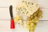 Cheese with mold and grapes on white wooden background close-up — Stock Photo