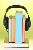Headphones on books on green background — Stock Photo