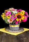 Beautiful bouquet of bright flowers on wooden table on black background — Stock Photo
