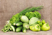 Fresh green vegetables on sackcloth background — Stock Photo