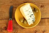 сыр с плесенью и оливки на пластине и нож на деревянных фоне крупным планом — Стоковое фото