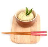 Macarrão asiático na tigela na placa de madeira, isolada no branco — Foto Stock