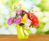 Bright green bucket with flowers on green background — Stock Photo
