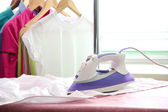 Electric iron and shirt, on cloth background — 图库照片