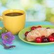 Croissant with cherries and coffee on wooden table on green background — Stock Photo #12317580