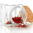 Stigmas of the saffron poured out a glass jar isolated on white - Stock Photo