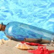 Glass bottle with note inside on sand, on blue sea background - Stock Photo