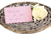 Beautiful rose on wicker mat with card isolated on white — Stock Photo