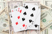 Dollars and a deck of playing cards on black background close-up — Stock Photo