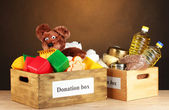 Donation box with food and children's toys on brown background close-up — Stock Photo