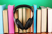 Headphones on books on wooden table on turquoise background — 图库照片