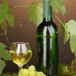 Bottle of great wine with glass on wooden table on brown background - Stock Photo