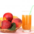 Ripe peaches and juice on wooden table on white background — Stock Photo