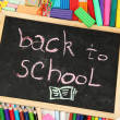 The words 'Back to School' written in chalk on the small school desk with various school supplies close-up — Stock Photo