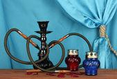 Cachimbo de água sobre uma mesa de madeira sobre um fundo de close-up cortina azul — Fotografia Stock